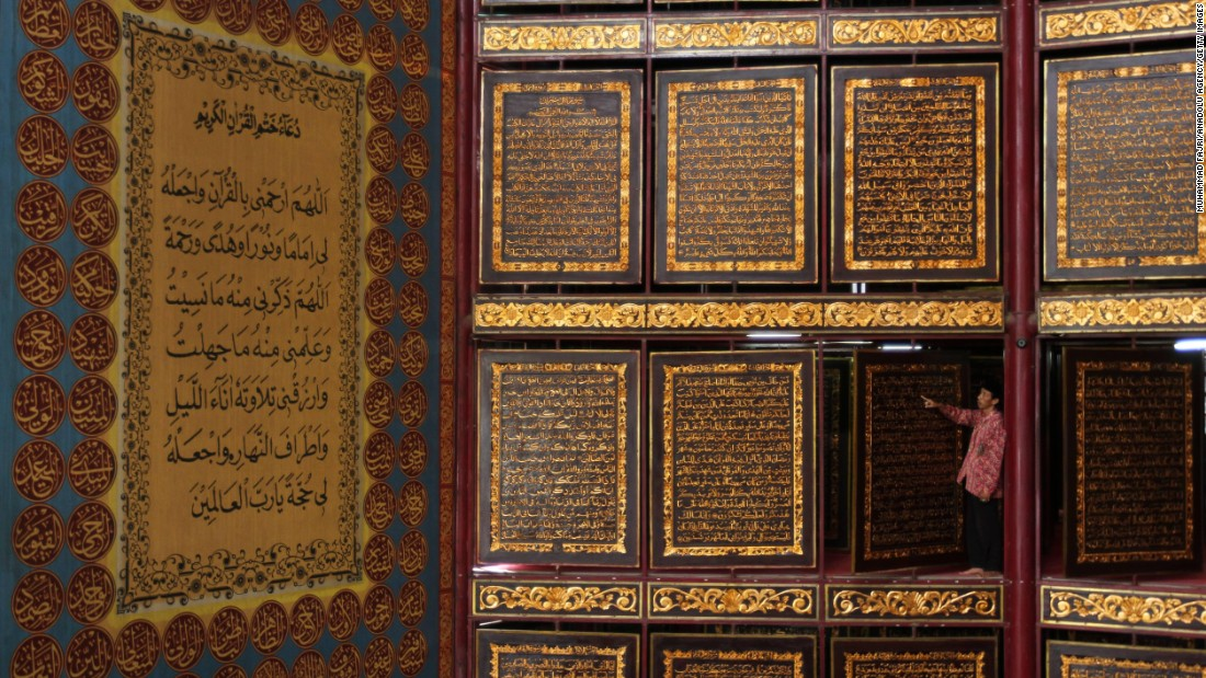 A man reads a large Quran made of carved wood at a school in Palembang, Indonesia, on Thursday, June 9.Ramadan, the most sacred month in the Muslim year, started on June 5.