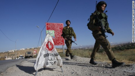 Israeli soldiers walk near a temporary checkpoint at the entrance of the Palestinian village of Yatta in the occupied West Bank on June 9,2016 after the army entered the village in search for clues leading to an attack the previous night in the Israeli city of Tel Aviv in which four people were killed and 16 others wounded.  The two Palestinians assailants who carried out the attack came from Yatta, according to Israeli authorities. Israel said it had suspended entry permits for 83,000 Palestinians during the holy Muslim month of Ramadan following the shooting attack.   / AFP / HAZEM BADER        (Photo credit should read HAZEM BADER/AFP/Getty Images)
