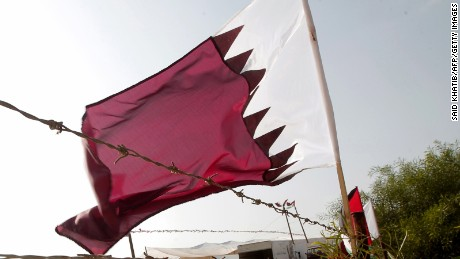 A Qatari flag flutters near a poster of Qatar's Emir Sheikh Hamad bin Khalifa al-Thani (L) at the construction site of a residential project funded by Qatar in Khan Yunis in the southern Gaza Strip on October 22, 2012.