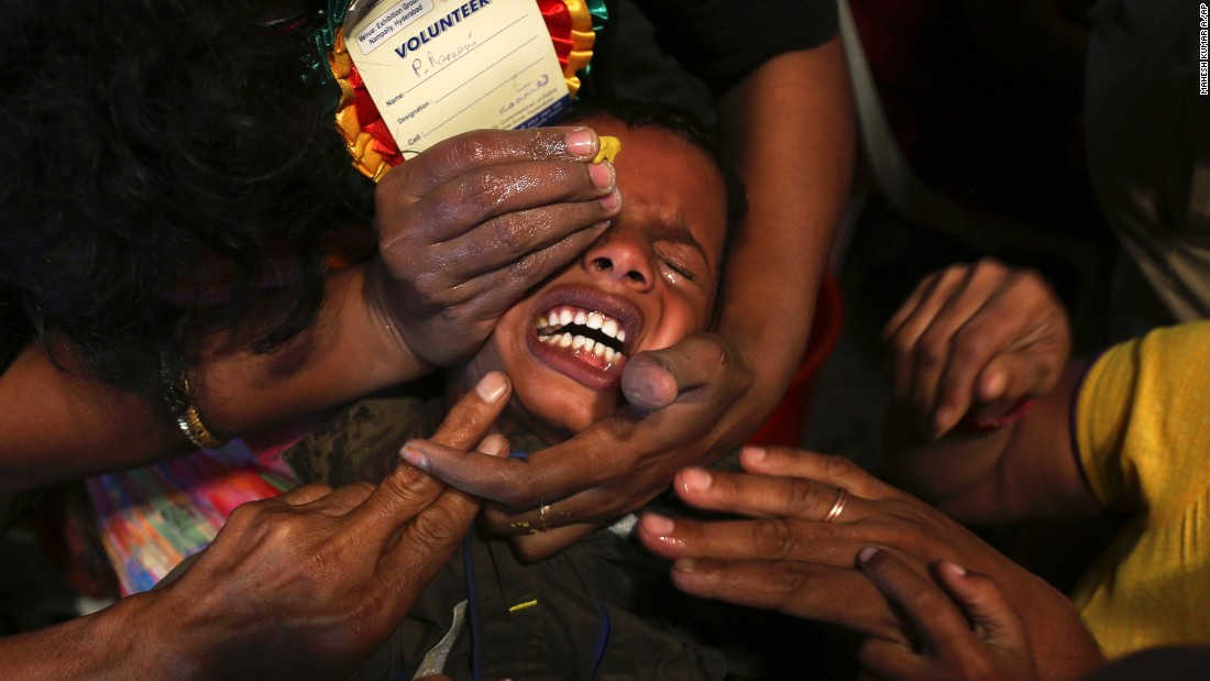 "People in Hyderabad, India, try to open the mouth of a child suffering from asthma so they can give him <a href=""http://www.cnn.com/2003/WORLD/asiapcf/south/06/10/offbeat.asthma.sardines/"" target=""_blank"">""fish medicine""</a> on Wednesday, June 8. The formula of herbs, handed down through generations, is inserted into a live sardine and then slipped into the patient's throat."
