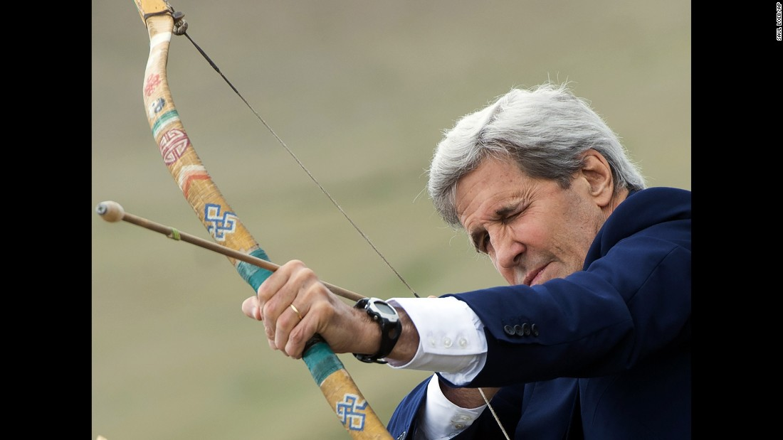 U.S. Secretary of State John Kerry shoots a bow and arrow in Ulaanbaatar, Mongolia, on Sunday, June 5. He was participating in a Naadam ceremony, a competition that traditionally includes archery, horse racing and Mongolian wrestling.