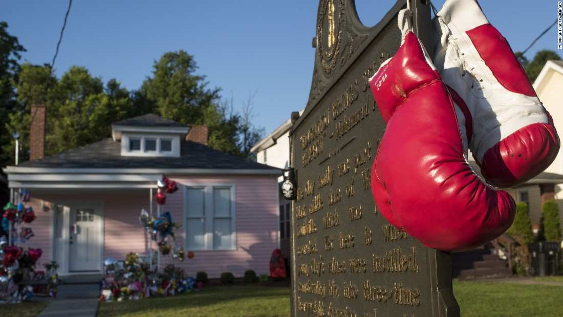 Boxing gloves hang from a historical marker in front of Ali's childhood home.