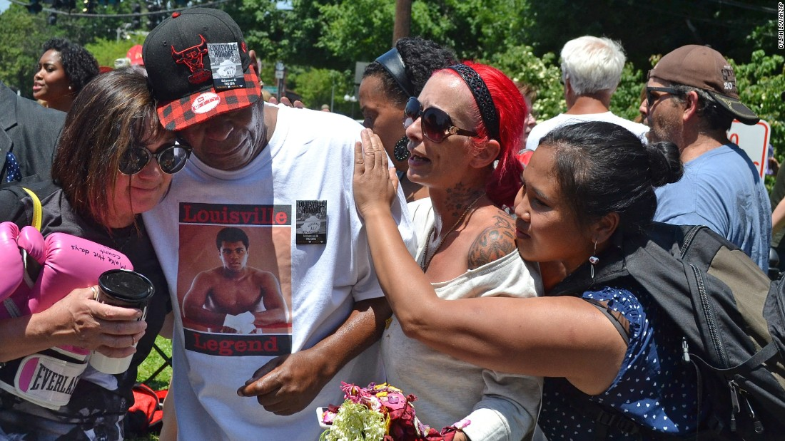 Gerald Wayne Jacobs is consoled by strangers as he cries at the cemetery's gates.
