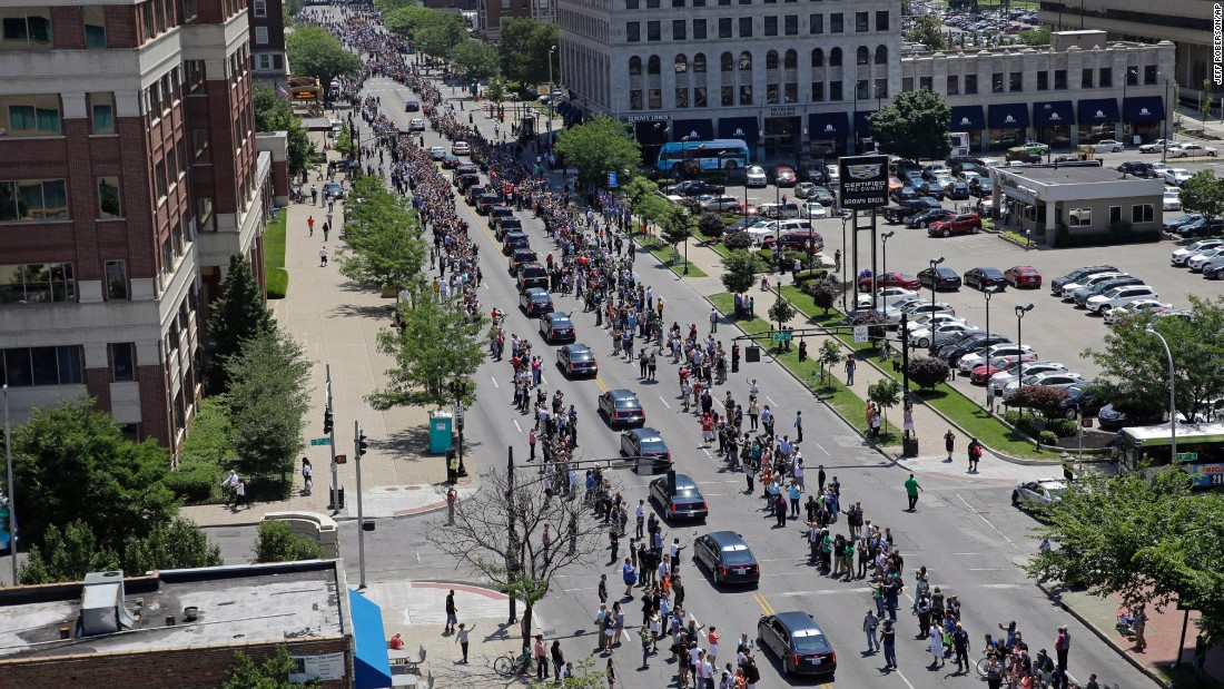 People line a street in Louisville to watch the funeral procession.