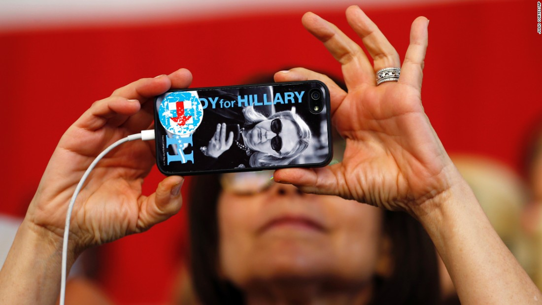 The likeness of Hillary Clinton is seen on a woman's phone as she takes a photo before Clinton's New York rally on Tuesday, June 7.