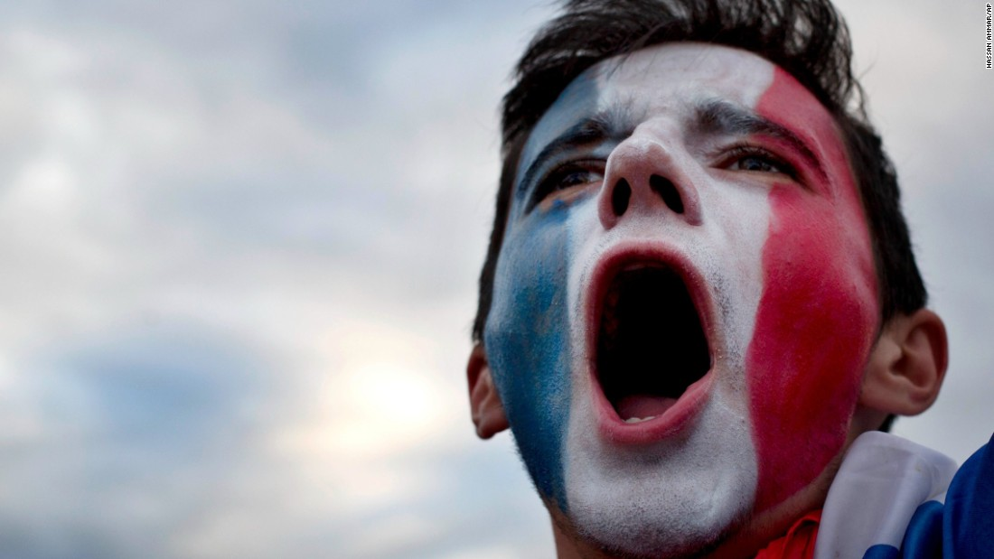 A France supporter, watching the match in Bordeaux, France, cheers during the national anthem.