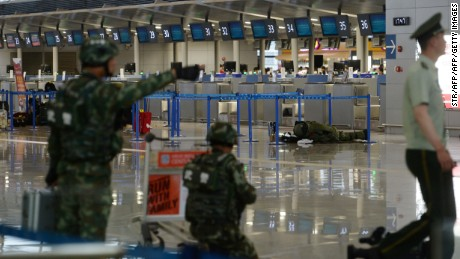A bomb disposal expert inspects luggage left near a check-in counter at Pudong Airport on June 12.