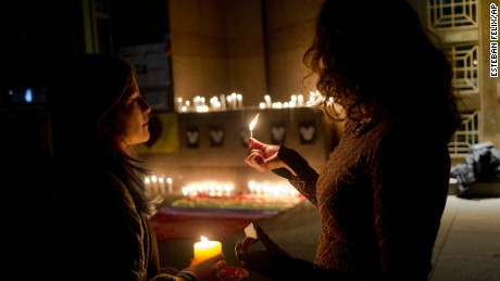 Two woman light candle during a vigil in front of the U.S. embassy to remember the victims of the mass shooting at the Pulse Orlando, Fla. nightclub, in Santiago, Chile, Sunday, June 12, 2016. A gunman opened fire inside the nightclub early Sunday, killing at least 50 people before dying in a gunfight with SWAT officers, police said. (AP Photo/Esteban Felix)
