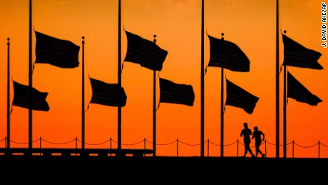 Runners pass under the the flags flying at half-staff around the Washington Monument at daybreak in Washington, Monday, June 13, 2016. The flags were ordered to half-mast by President Barack Obama to honor the victims of the Orlando nightclub shootings.