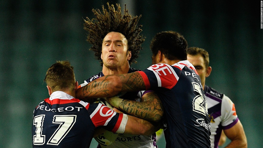 Kevin Proctor of the Melbourne Storm is tackled by Sydney Roosters during a National Rugby League match in Sydney on Saturday, June 11.