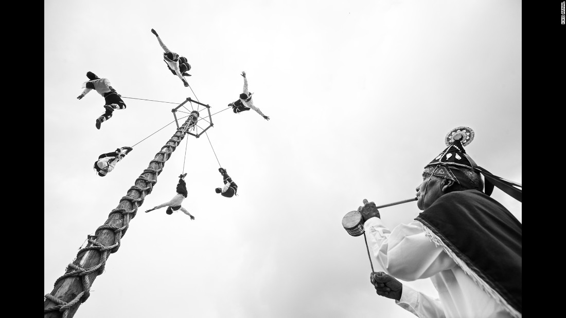Young voladores descend from a pole while their teacher plays the flute and drum.