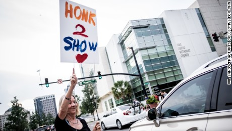 A woman holds up a sign urging solidarity in downtown Orlando on Monday. The community showed signs of resilience.