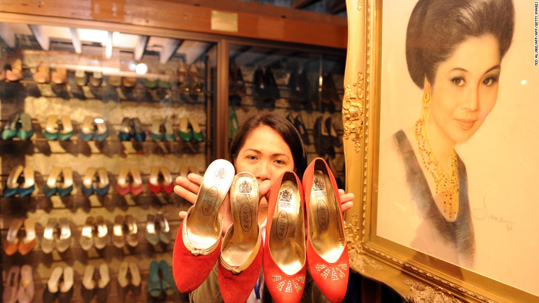 A museum employee displays some of the hundreds of shoes belonging to former Philippine first lady Imelda Marcos, next to her portrait (R) at the shoe museum in Manila on September 26, 2012.