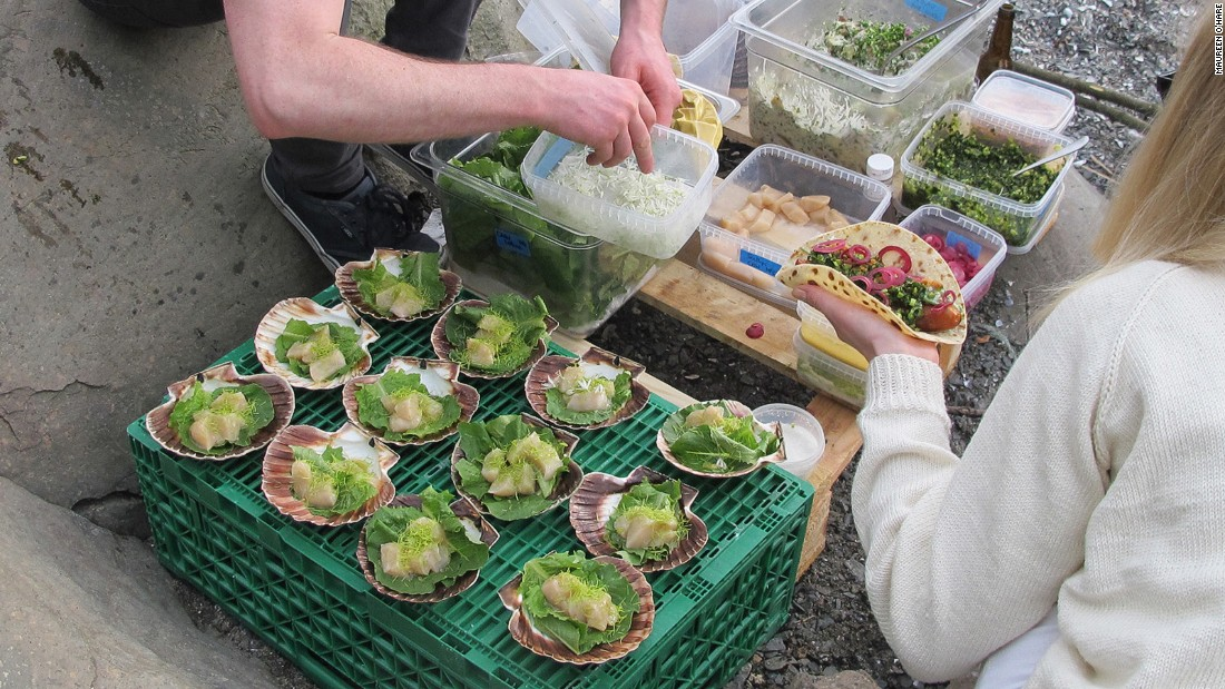 Staff from Maaemo prepare polses (hot dogs) and scallops served in shells with ramsen, or wild garlic.
