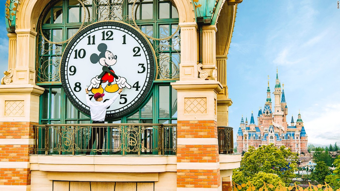 A Shanghai Disneyland cast member sets the theme park's Mickey Avenue clock prior to the official June 16 opening.