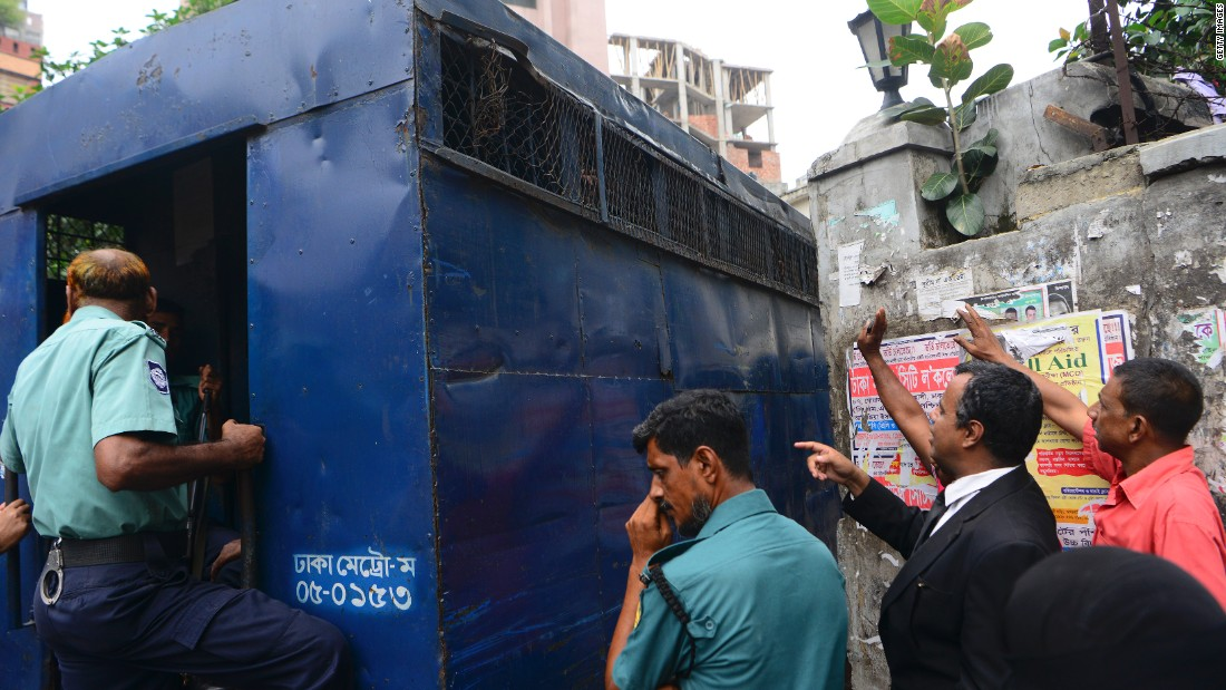 The arrested men try to talk with relatives and lawyers from a prison van outside court.
