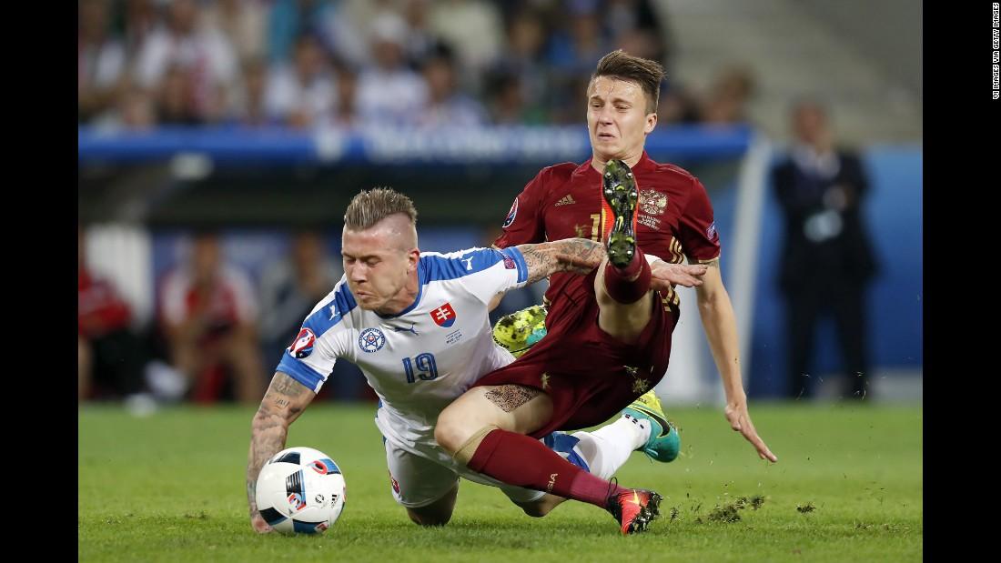 Slovakia's Juraj Kucka, left, competes against Russia's Aleksandr Golovin.