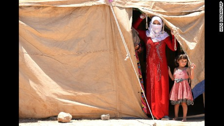 Internally displaced Iraqis peer out of a tent at a camp outside Falluja, Iraq, on Monday, June 14.