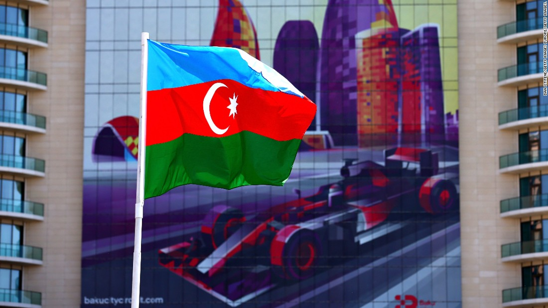 The Azerbaijan flag flutters in front of a poster promoting the European Grand Prix in Baku.