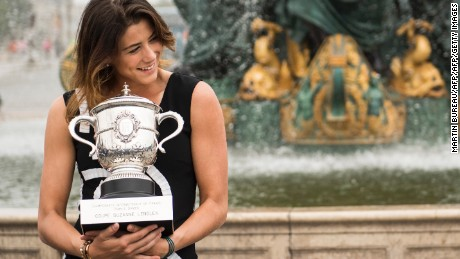 Spain's Garbine Muguruza poses for photographers with her trophy one day after winning her women's final match against US player Serena Williams at the Roland Garros 2016 French Tennis Open on June 5, 2016 at Place de la Concorde in Paris. / AFP / MARTIN BUREAU        (Photo credit should read MARTIN BUREAU/AFP/Getty Images)