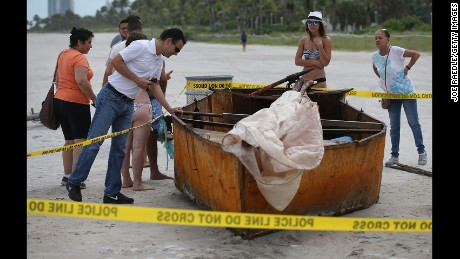 People look at a Cuban migrant boat that brought 12 people and a dog to the beach on September 15, 2015 in Miami Beach, Florida under the previous wet-foot, dry-foot policy.
