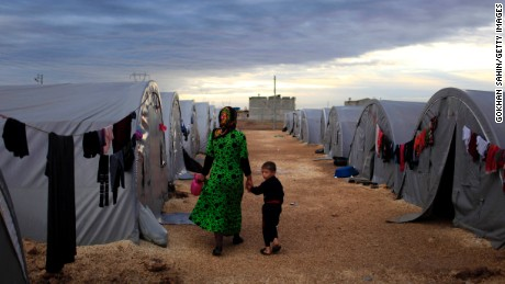 A Kurdish refugee mother and son from the Syrian town of Kobani walk beside their tent in a camp in the southeastern town of Suruc on the Turkish-Syrian border on October 19, 2014 in Sanliurfa, Turkey.  Kurdish fighters in Syrian city of Kobani have pushed back Islamic State militants in a number of locations as U.S. air strikes on ISIS positions continue in and around the city. In the past month more than 200,000 people from Kobani have fled into Turkey.