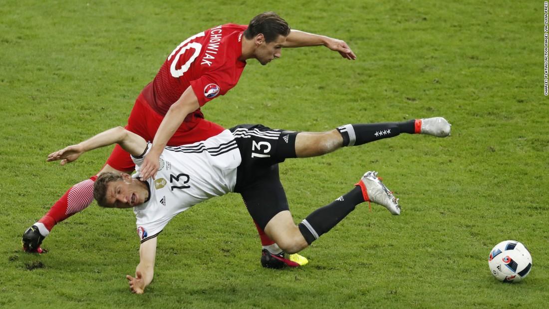 Germany's Thomas Muller falls near Poland's Grzegorz Krychowiak.