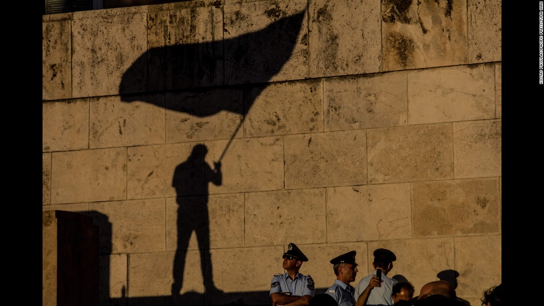 Police in Athens, Greece, watch a man wave a flag during an anti-government demonstration outside Parliament on Wednesday, June 15.