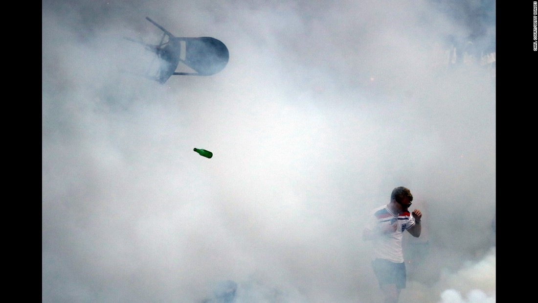 "A bottle and a chair go flying as an England soccer fan walks through tear gas in Marseille, France, on Friday, June 10. <a href=""http://www.cnn.com/2016/06/12/world/euro-2016-england-russia-violence/"" target=""_blank"">Packs of England fans clashed with Russian fans</a> over the weekend as the two countries faced off in the European Championship."