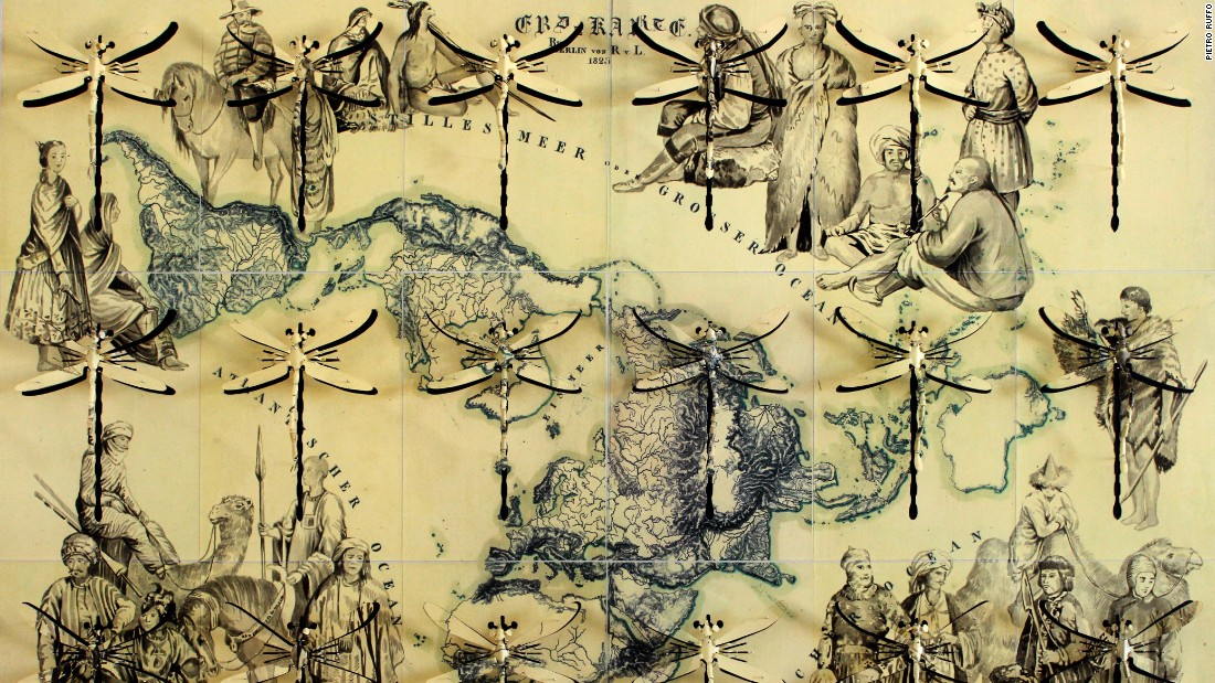 "In ""Atlante del Popoli"" (Atlas of Peoples), 2015, large hand-carved dragonflies superimposed over a map of the world represent the idea of freedom."