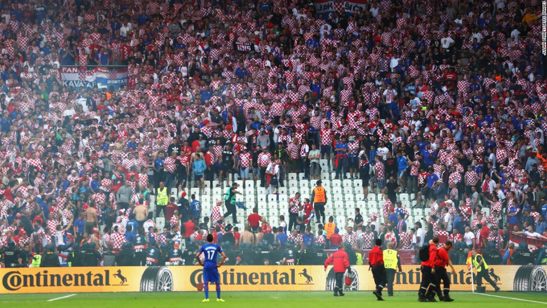 Croatian fans are seen in the crowd as the flares are taken off the field.