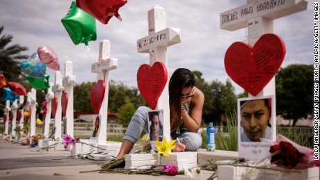 ORLANDO, FL - JUNE 17: A woman writes a note on a cross for Eric Ivan Ortiz-Rivera at a memorial with wooden crosses for each of the 49 victims of the Pulse Nightclub, next to the Orlando Regional Medical Center, June 17, 2016 in Orlando, Florida. The shooting at Pulse Nightclub, which killed 49 people and injured 53, is the worst mass-shooting event in American history. (Photo by Drew Angerer/Getty Images)