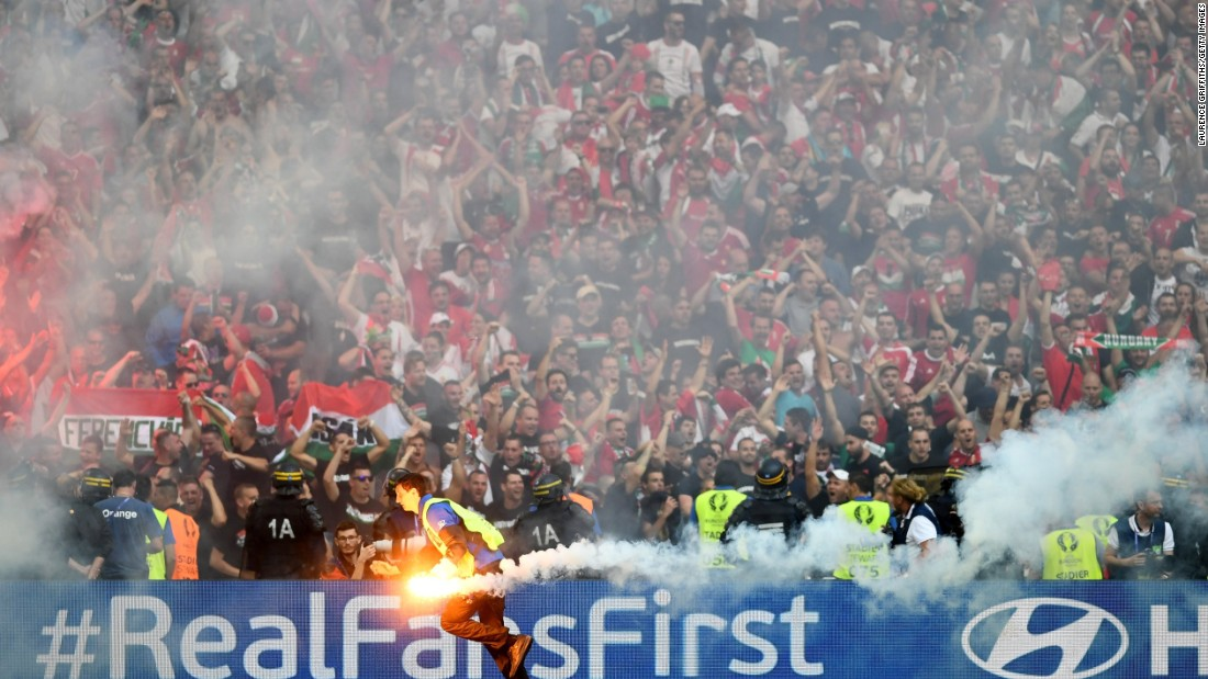 A steward picks up a flare which was thrown onto the pitch by fans.