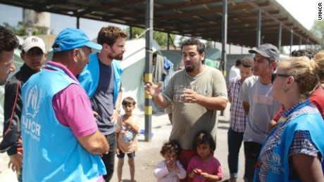 Theo James talks to refugees at a camp at Alexanderia in Greece, which is home to 812 refugees, the majority of them from Syria and Iraq.