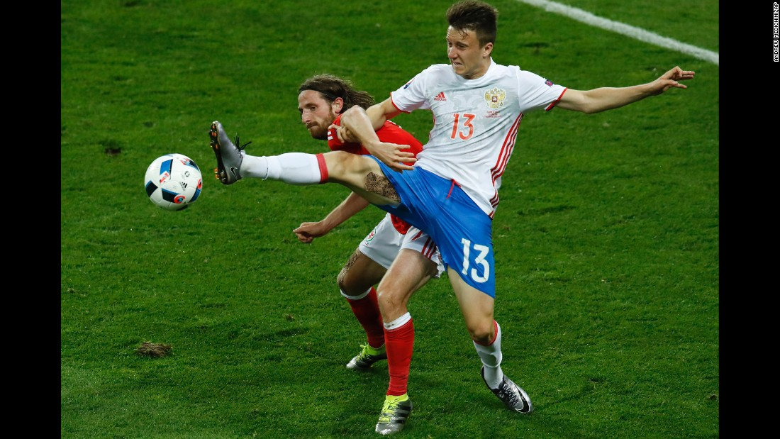 Russia's Aleksandr Golovin, right, battles Joe Allen for possession.
