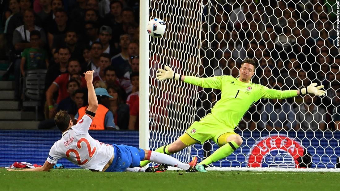 Welsh goalkeeper Wayne Hennessey makes himself big near Russian forward Artem Dzyuba.