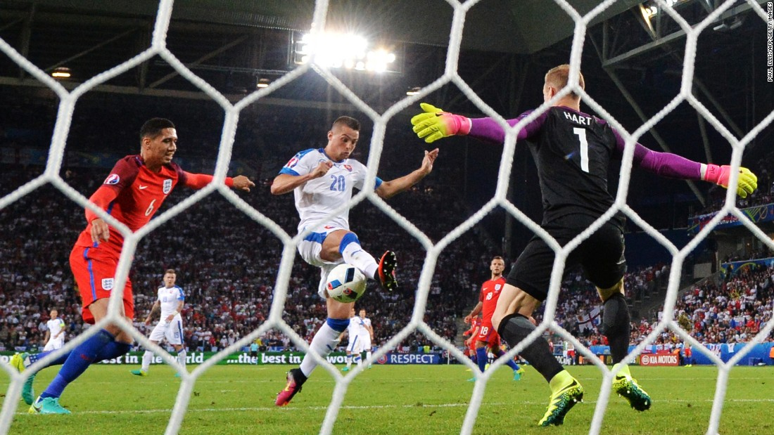 English goalkeeper Joe Hart makes a save on Slovakia's Robert Mak during the two teams' scoreless draw in Saint-Etienne, France. England finished second in the group and is assured of a place in the next round of the tournament. Slovakia finished in third and will have to wait until the end of the group stage to see if they will advance.