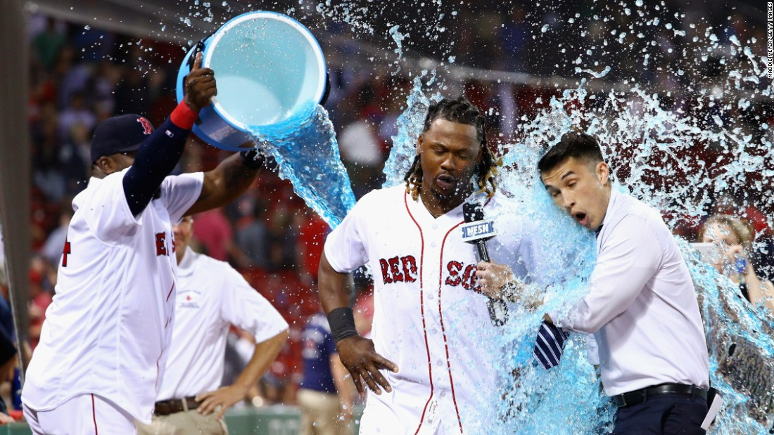 David Ortiz douses Boston teammate Hanley Ramirez and NESN reporter Gary Striewski after the Red Sox defeated Baltimore on Wednesday, June 15.