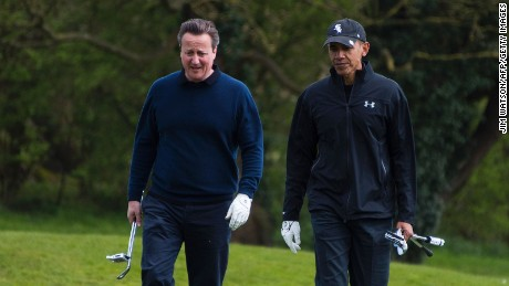 US President Barack Obama (R) talks with British Prime Minister David Cameron (L) as they walk onto the 3rd green at The Grove Golf Course near Watford in Hertfordshire, north of London, on April 23, 2016.
