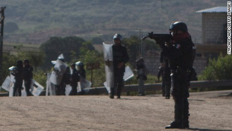Members of Mexican Federal Police clash with teachers holding a protest against an education reform and the arrest of two of its leaders, in Oaxaca State, on June 19, 2016.  At least three people were killed and dozens injured when police clashed with thousands of teachers blocking roads in a protest in southern Mexico on Sunday, leaving some officers with bullet wounds. / AFP / STR        (Photo credit should read STR/AFP/Getty Images)