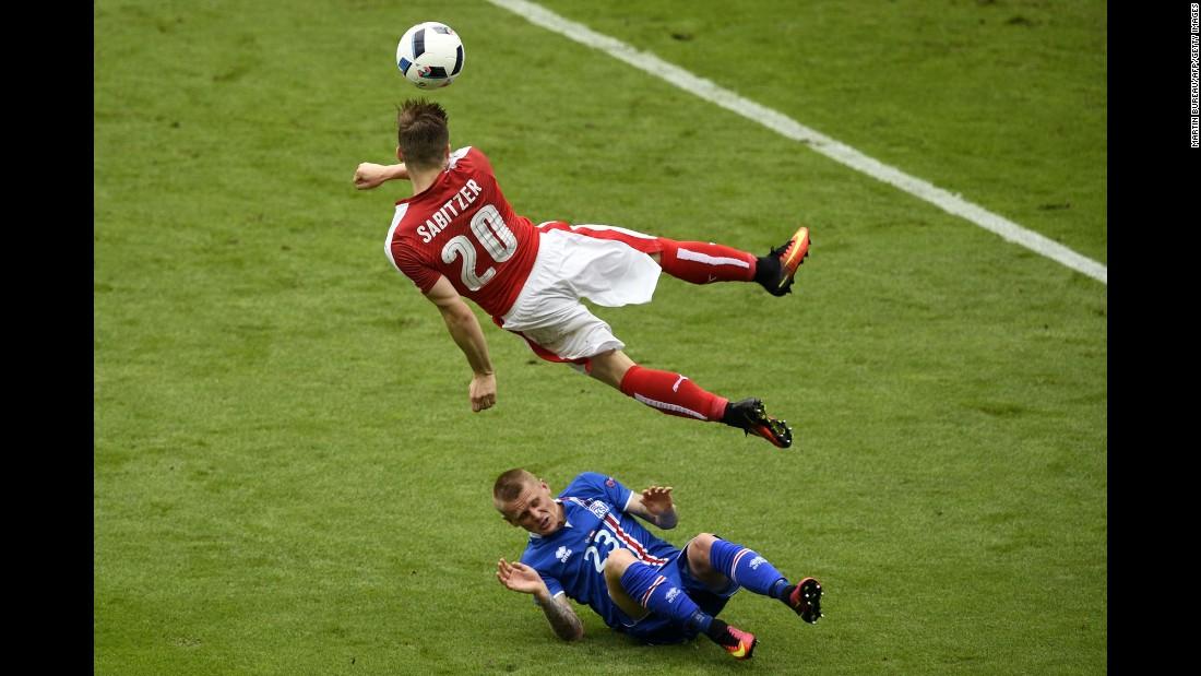 Iceland defender Ari Skulason slides under Austria's Marcel Sabitzer.