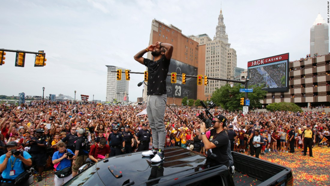 Cavaliers guard Kyrie Irving stands on the roof of a pickup truck to greet fans before the start of the parade.