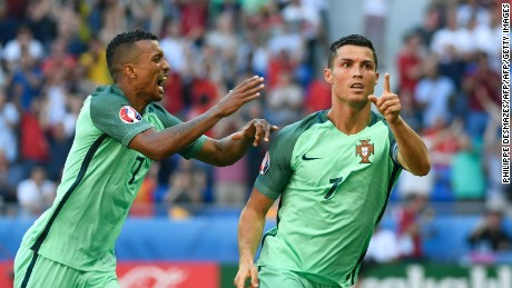 Portugal's forward Cristiano Ronaldo (R) celebrates after scoring a goal  during the Euro 2016 group F football match between Hungary and Portugal at the Parc Olympique Lyonnais stadium in Decines-Charpieu, near Lyon, on June 22, 2016. / AFP / PHILIPPE DESMAZES        (Photo credit should read PHILIPPE DESMAZES/AFP/Getty Images)