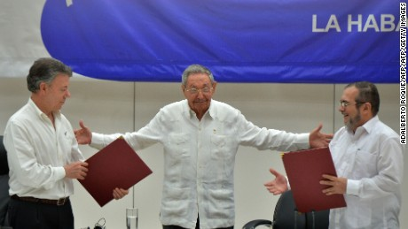 "Colombia's President Juan Manuel Santos (L) and Timoleon Jimenez, aka ""Timochenko"" (R), head of the FARC leftist guerrilla, hold folders with documents as Cuban President Raul Castro (C) gestures during the signing of the ceasefire in Havana on June 23, 2016. Colombia's government and the FARC guerrilla force signed a definitive ceasefire Thursday, taking one of the last crucial steps toward ending Latin America's longest civil war. / AFP / ADALBERTO ROQUE        (Photo credit should read ADALBERTO ROQUE/AFP/Getty Images)"
