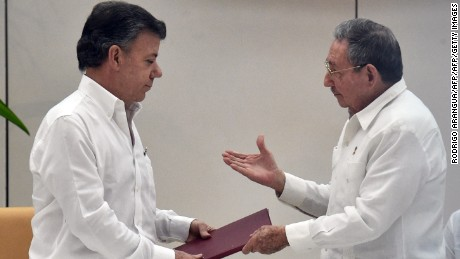 "Colombian President Juan Manuel Santos (L) exchanges documents with Cuban President Raul Castro (R) during a meeting with the head of the FARC guerrilla Timoleon Jimenez, aka Timochenko (out of frame) in Havana on September 23, 2015. The Colombian government and FARC rebels announced a key breakthrough in their nearly three-year peace talks Wednesday with the signing of a deal on justice for crimes committed during the five-decade conflict. The deal includes the creation of special courts and a broad amnesty, though this will not cover ""crimes against humanity, serious war crimes"" and other offenses including kidnappings, extrajudicial executions and sexual abuse, said officials from Cuba and Norway, the guarantors in the talks. AFP PHOTO / Rodrigo ARANGUA        (Photo credit should read RODRIGO ARANGUA/AFP/Getty Images)"