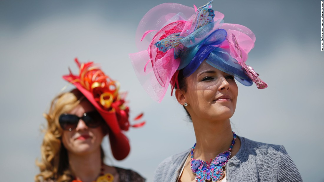 Two visitors to the 167th Prix de Diane, a flat race in Chantilly, France, provide a splash of color with their headwear.
