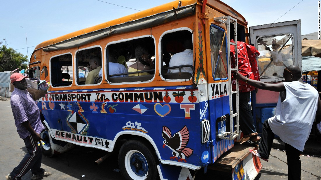 People boarding a car rapides bus, the distinctive yellow and blue buses of Dakar  are decorated with bright images or praise for religious leaders.