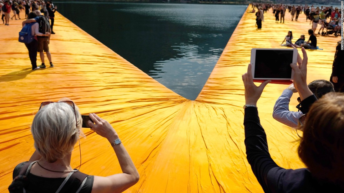 Visitors take pictures and walk across floating orange piers Saturday, June 18, as part of Christo's art project on Italy's Lake Iseo.