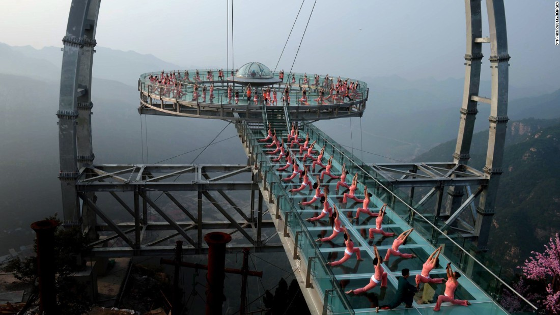 People practice yoga on a sightseeing platform in Beijing on Monday, June 20.