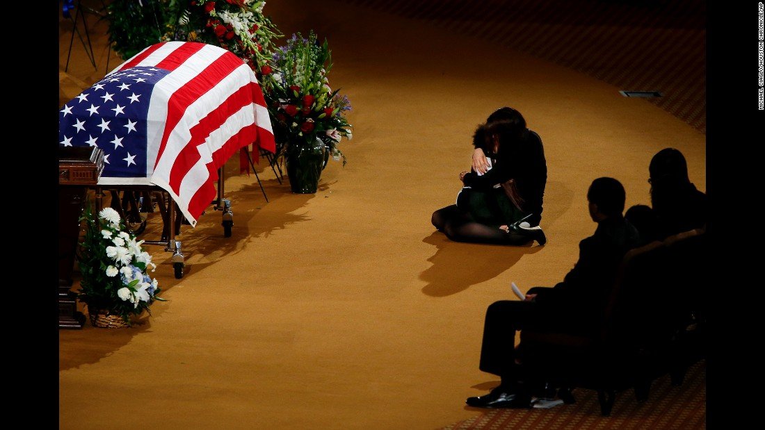 Lucy Lugo, wife of fallen police officer Endy Ekpanya, comforts their son, Julian, during his funeral service in Houston on Tuesday, June 21. Ekpanya, a police officer in Pearland, Texas, died after his patrol car was struck by another vehicle.